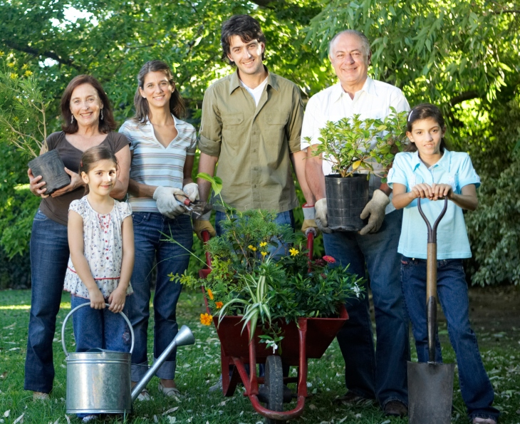 Three generation family including children (7-11) with gardening tools in garden, portrait